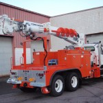 Radial boom derrick attachment on commercial truck