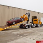 Hooklift truck attachment lifting car.