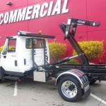 White truck with hooklift attachment.