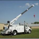 Service truck with extended crane.