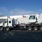 Commercial truck with stiff boom crane
